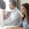 Millennial female call center agent wear headset with microphone consult customer online on pc in coworking space, focused woman employee in earphones busy working on computer in shared office