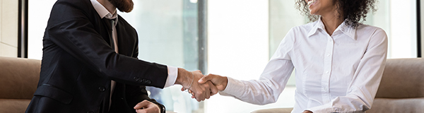 Smiling multiracial businesspeople shake hands greeting or get acquainted at business office meeting, happy diverse multiethnic colleagues or partners handshake close deal after successful negotiation