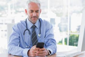 Physican Doctor Stethoscope Around Neck Looking At Mobile Phone