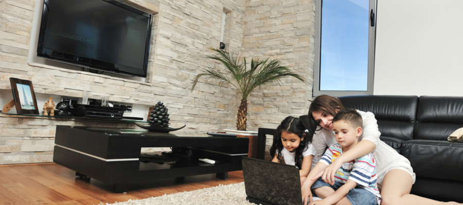 Mother and young girl and boy on laptop in living room